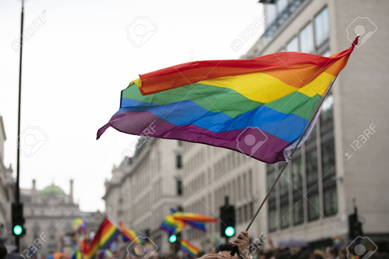 Gay pride, LGBTQ rainbow flags being waved in the air at a pride event - 131557891