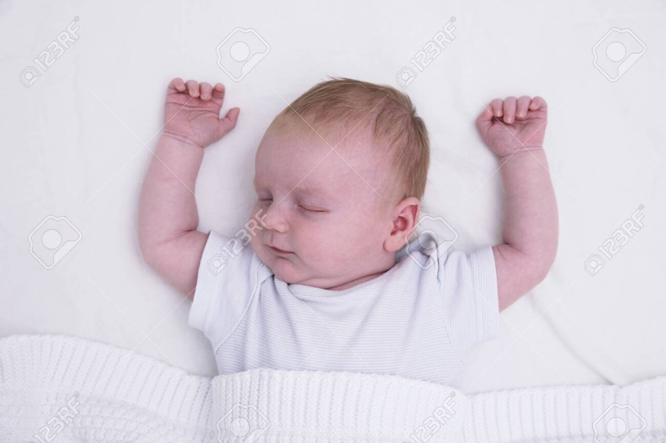 A sleeping young baby with their arms up. Cute baby asleep - 132860704