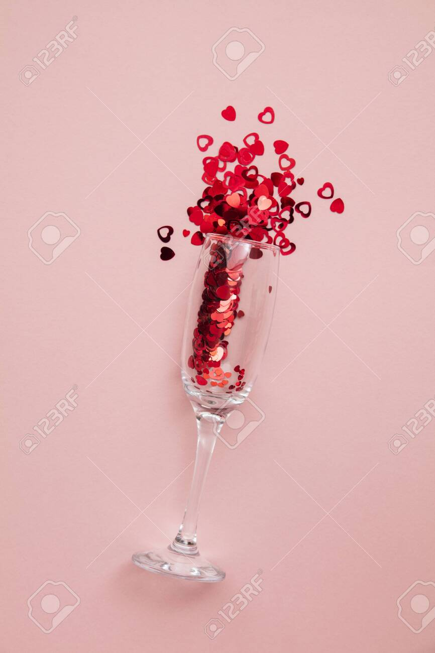 Valentine's day date night background. Drinks glasses with red heart confetti. - 139021569
