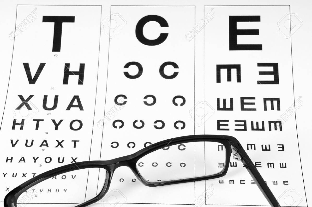 Reading Eyeglasses And Eye Chart Close Up On A Light Gray Background