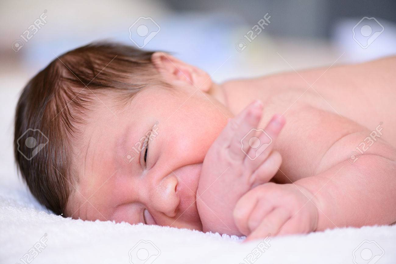 After Childbirth Newborn Baby Sleeping In A Bed With A Diaper Stock