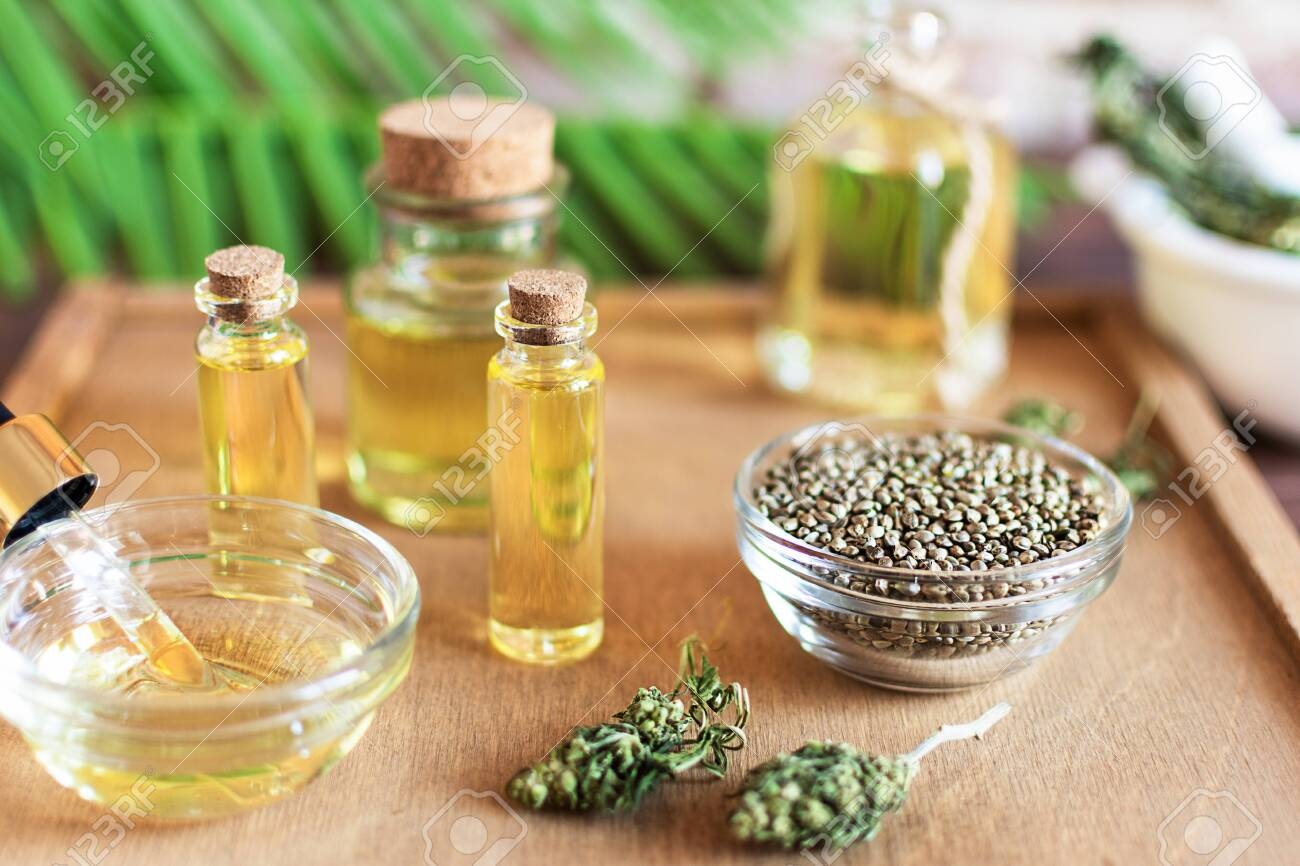 Bottles of hemp oil with cannabis seeds and dry leaves on white wooden table. Medical CBD oil. Alternative medicine concept. - 144140864