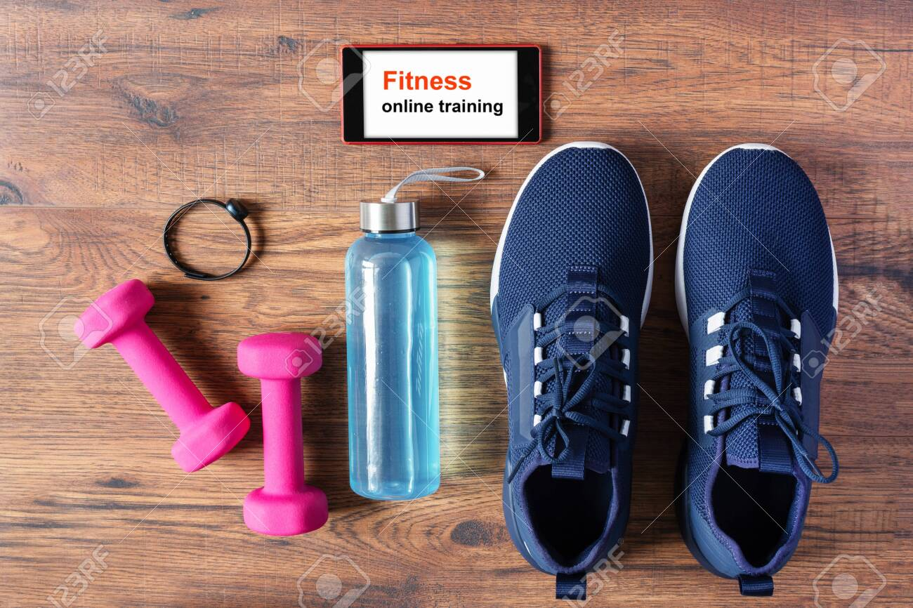 Fitness equipment, sport shoes and smartphone on wooden background top view. App for sport training indoors. Online Fitness training concept. Online workout staying at home. - 147424864