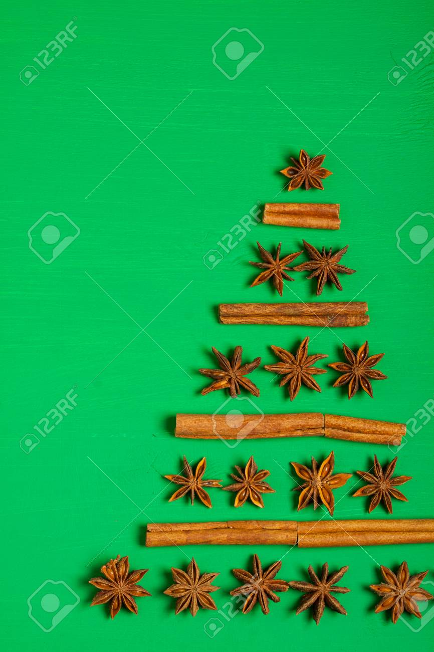 Anise And Cinnamon Spices Christmas Tree Shape On Green Background Vertical Orientation Top View