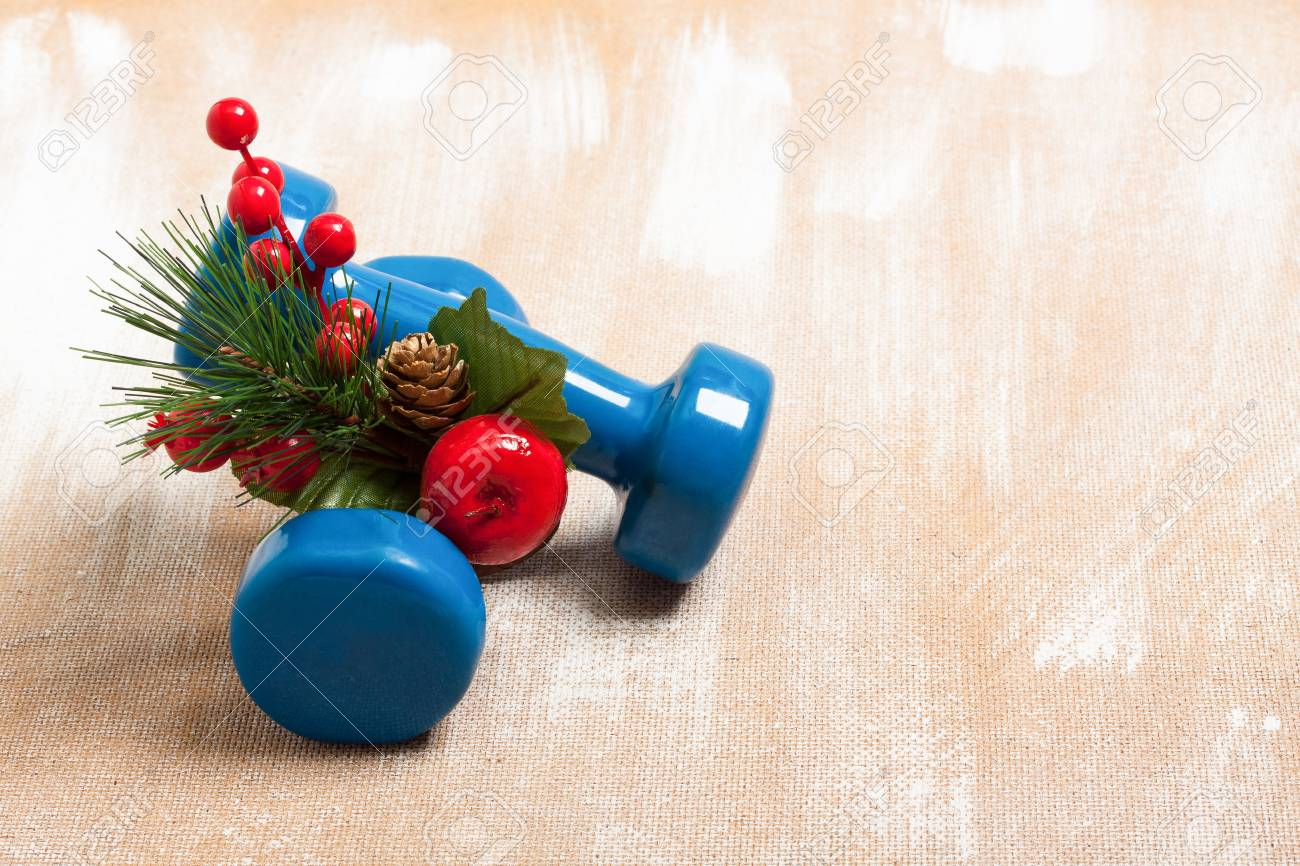 Christmas Sports Background.Christmas Sport Composition With Dumbbells Red Berries And Spruce