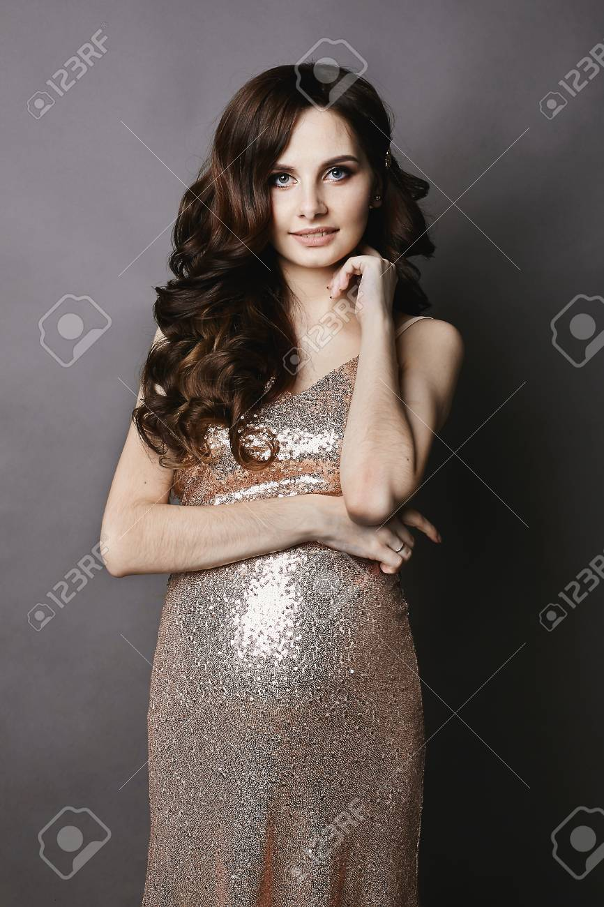 3b4cd0c678eb6 Stock Photo - Young and beautiful pregnant brunette woman with gentle makeup,  in the shiny gold dress, smiling and posing at the grey background at a  studio
