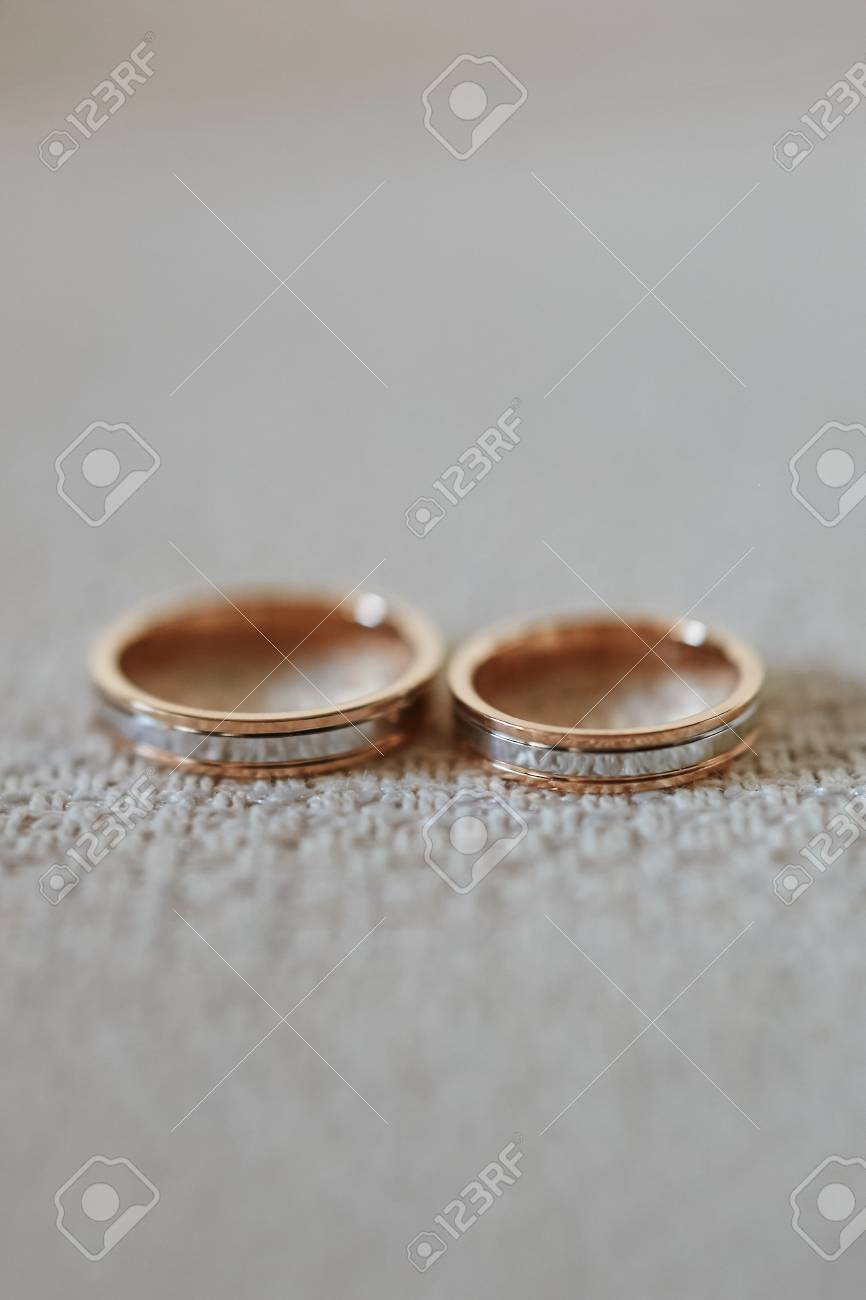 Close up view of stylish gold wedding rings on the textile. - 117879697