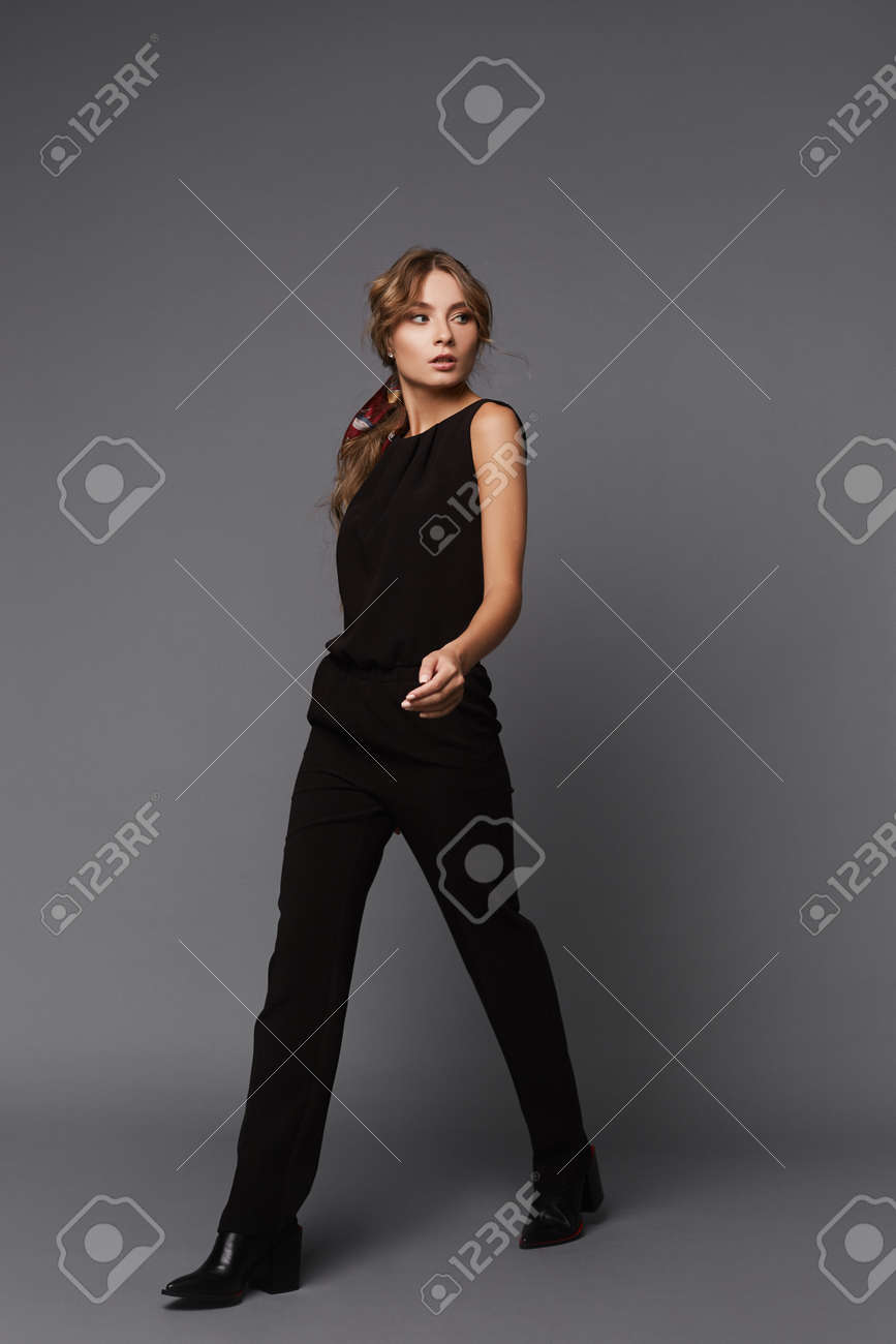 A young woman in a black casual outfit walking over the grey background. Model girl in a black suit on the grey background - 165777569