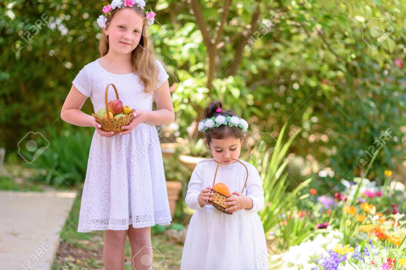 Harvest. Shavuot. Two cute smiling little girls holds basket with fruits at the beautiful summer garden. Portrait adorable small kids outdoor. - 122011267