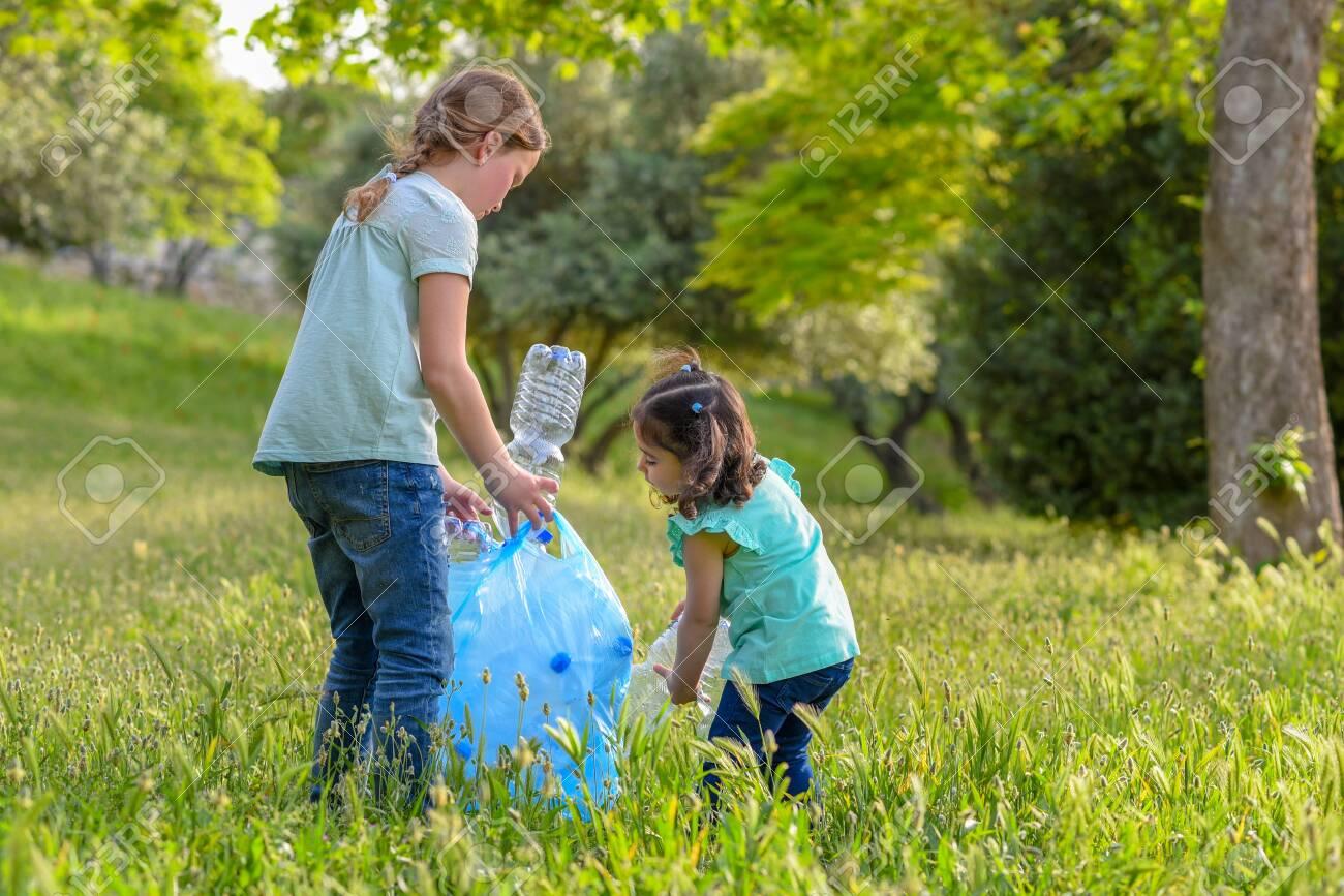 Little girls takings plastic bottles from grass. Children picking up litter in the park . - 123695528