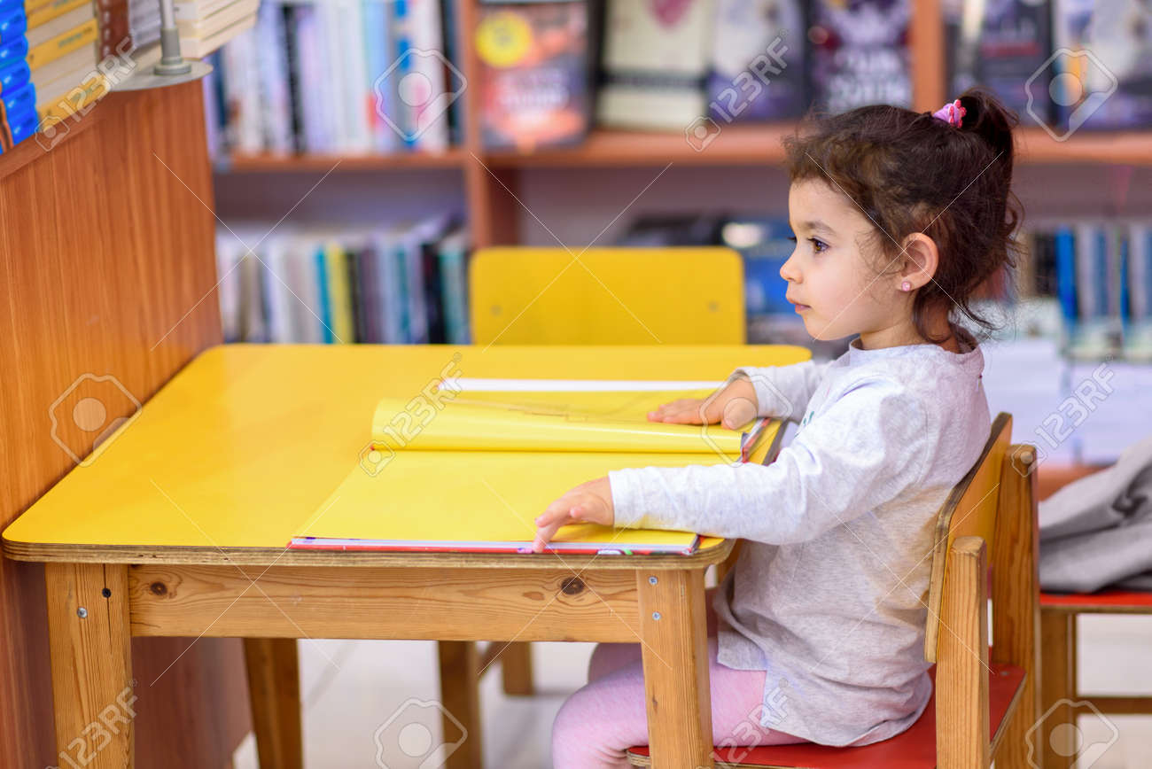 Little Girl Indoors In Front Of Books. Cute Young Toddler Sitting On A Chair Near Table and Reading Book. Child reads in a bookstore, surrounded by colorful books. Library, Shop, Shelving In Home. - 125789862