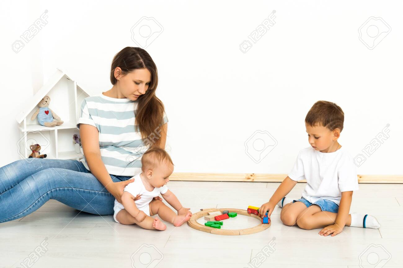 Motherhood. Spending time together. Mother Sitting With kids playing toys Indoors at home - 142862357