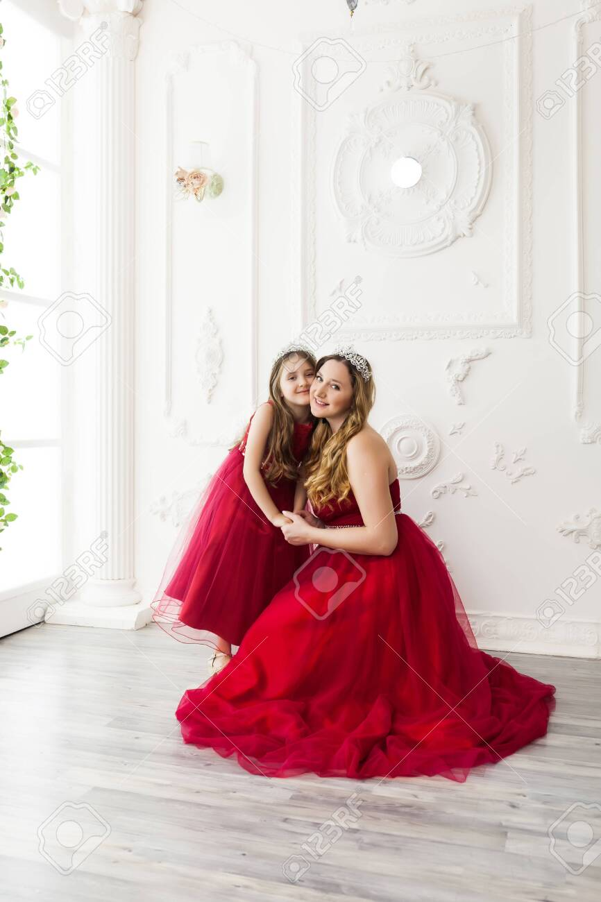 Mother and daughter in same outfits posing in the interior of the photo studio weared Red Dresses. Family look - 146954837
