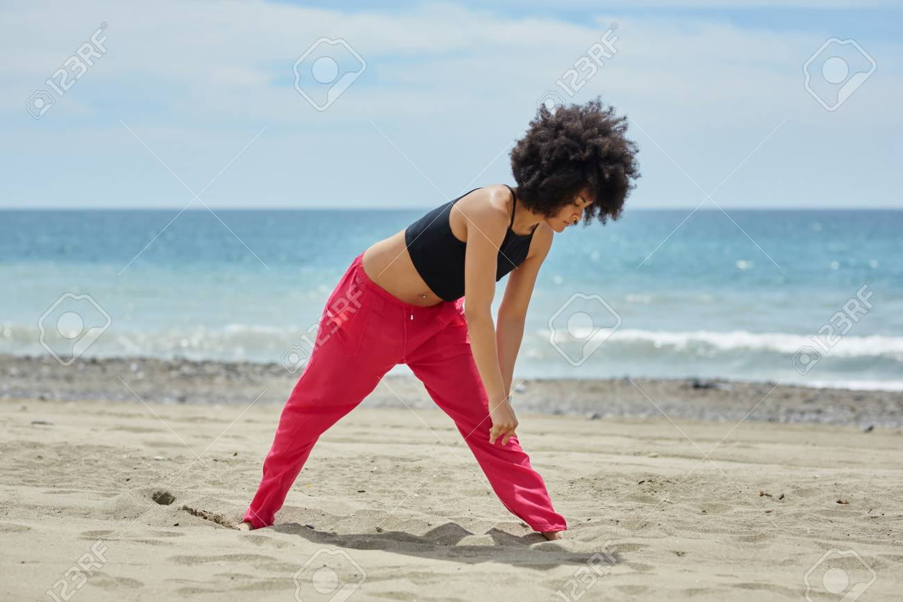young afro american sportswoman warming up on beach stock photo