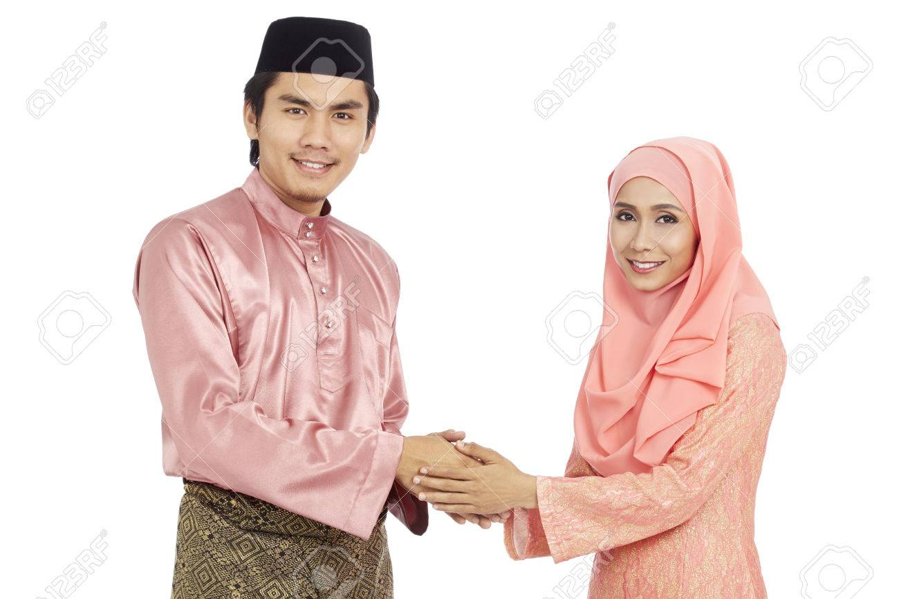 Couple In Traditional Malay Clothes Greeting Each Other With The