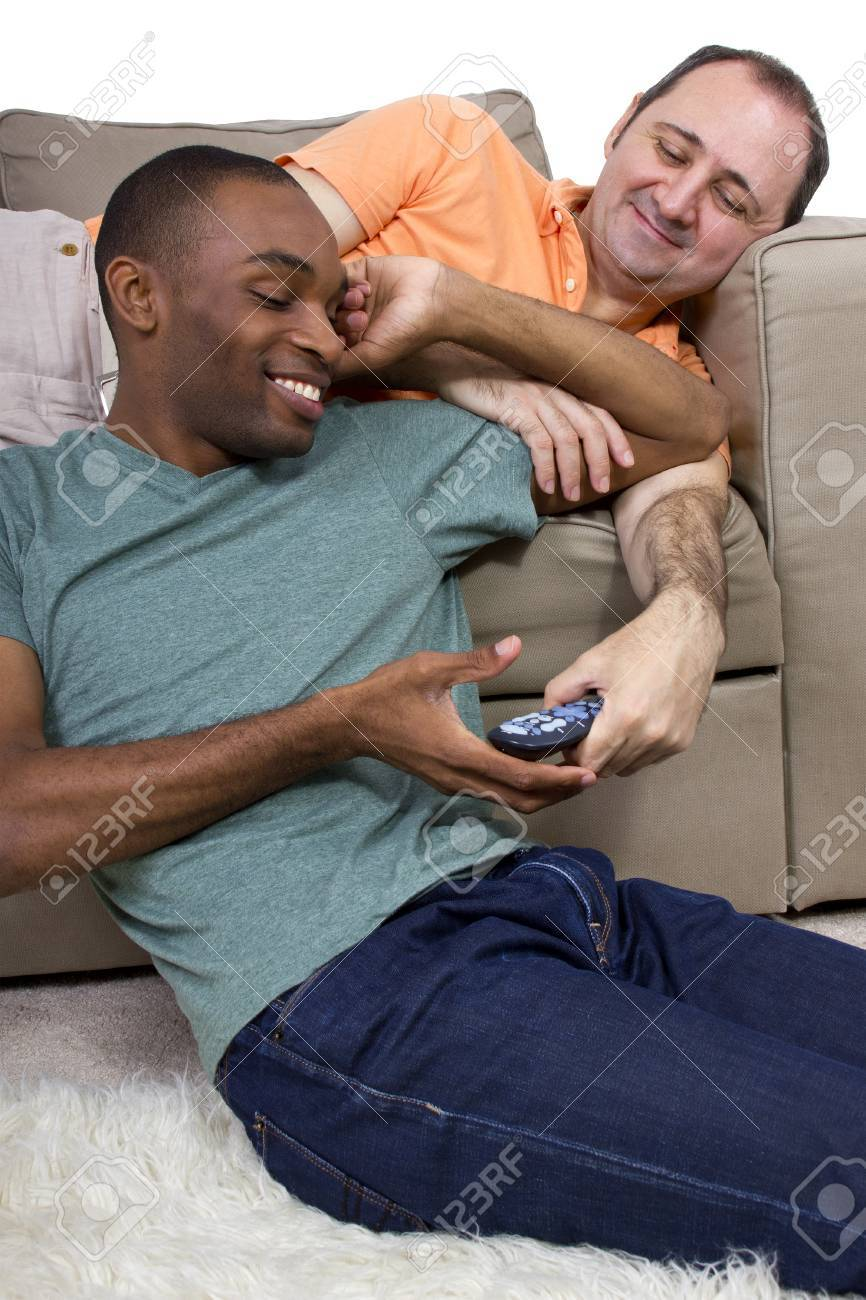 Gay Lovers two gay lovers relaxing at home in the livingroom stock photo