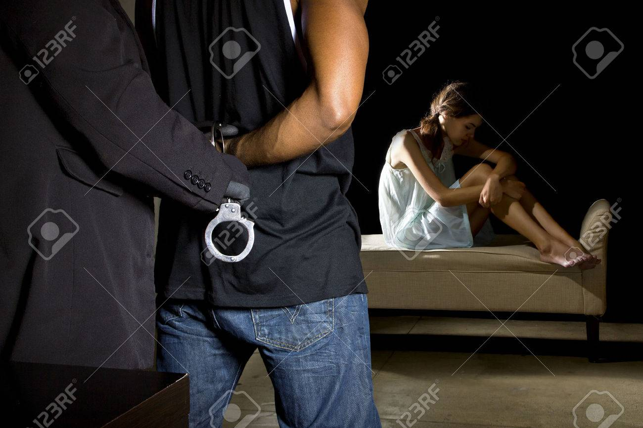 Cop arresting a man for domestic violence and female victim in the background - 38915255