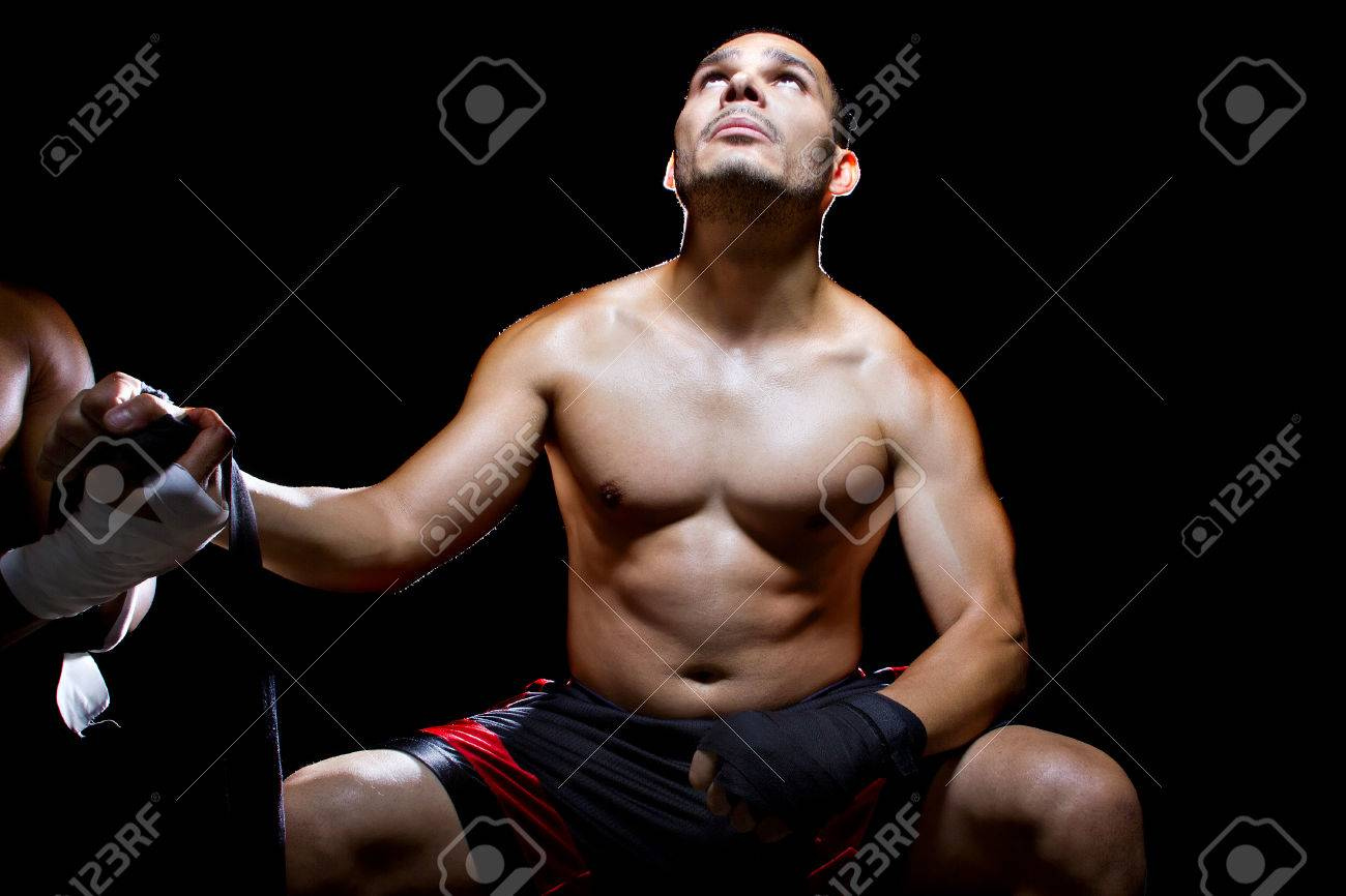 Latin boxer or mma fighter looking up in prayer for victory
