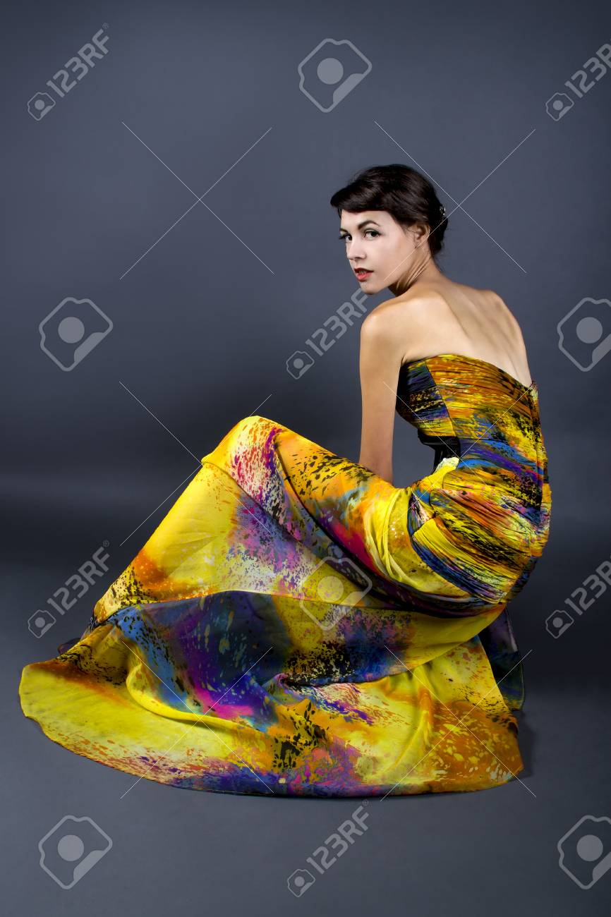 1cf60c2b Stock Photo - Woman wearing a yellow silk tie dye dress on a dark studio  background