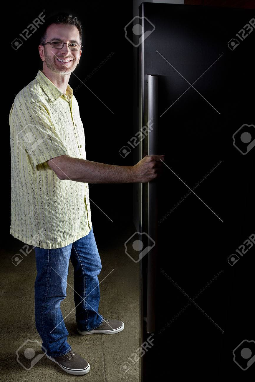 Dark Kitchen At Night man looking for food in an open fridge in a dark kitchen late