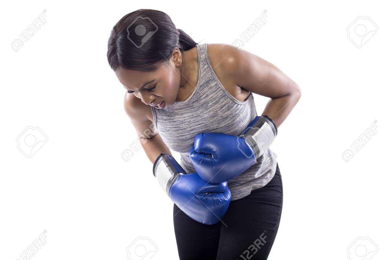 Black female on a white background wearing boxing gloves looking