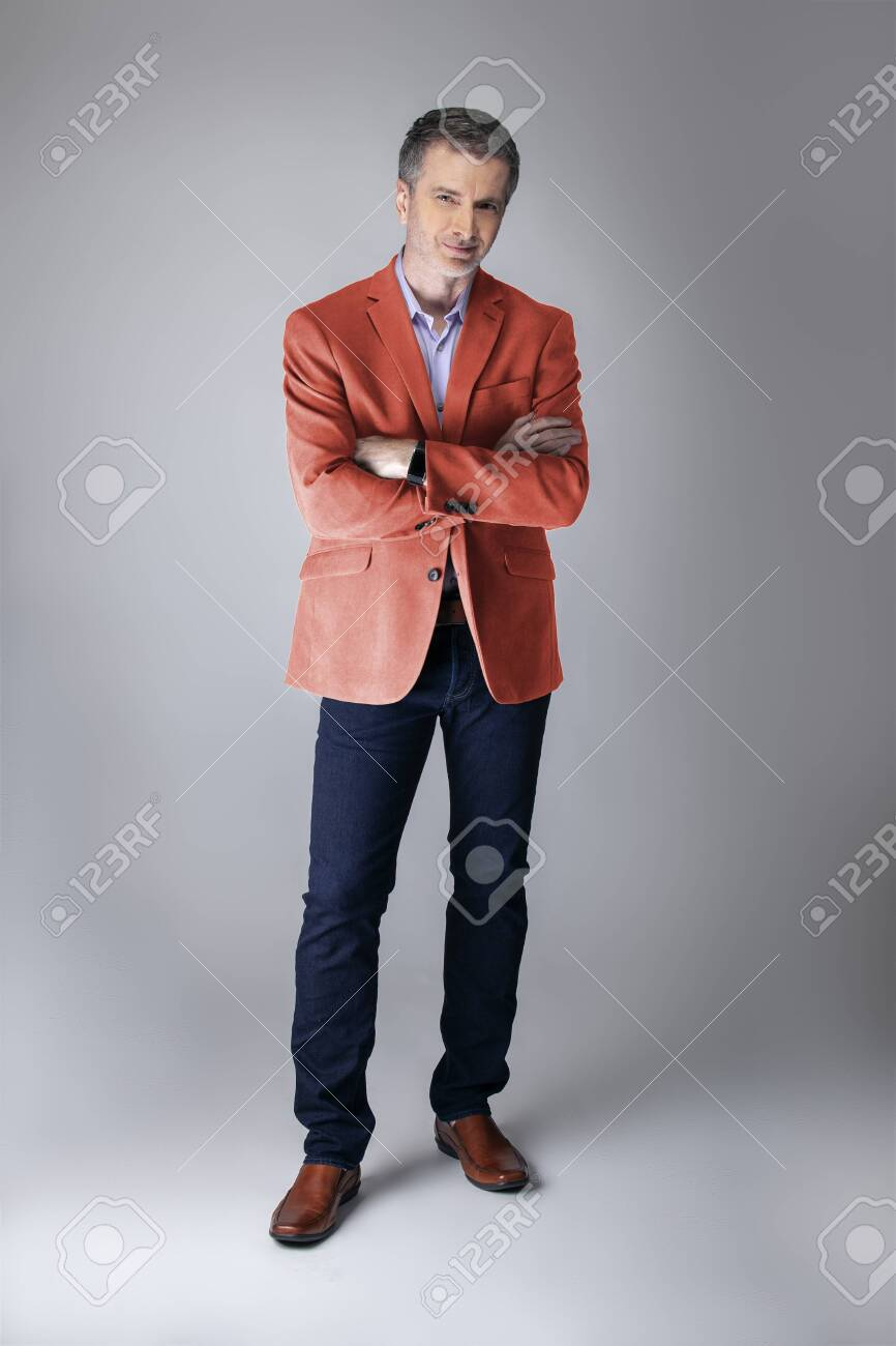 Middle-aged fashion model wearing coral colored sports coat or jacket for the fall clothing collection. Depicts modern colorful apparel style for 2019. - 127059516