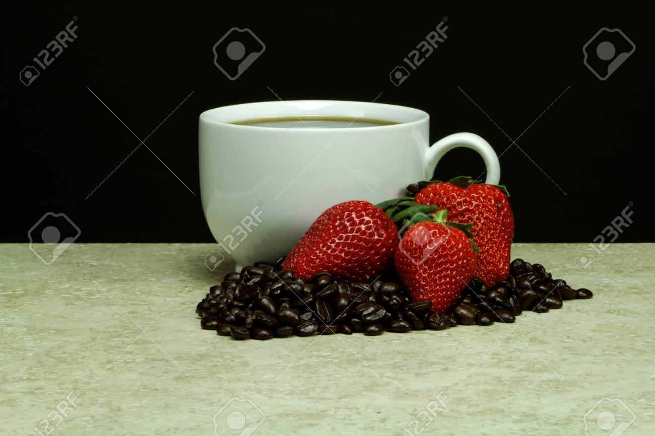 This white coffee cup is fill to the brim with strawberry falvored coffee   Dark rosted coffee beans contrast the cup accented by red, ripe delicious strawberries Stock Photo - 19102431
