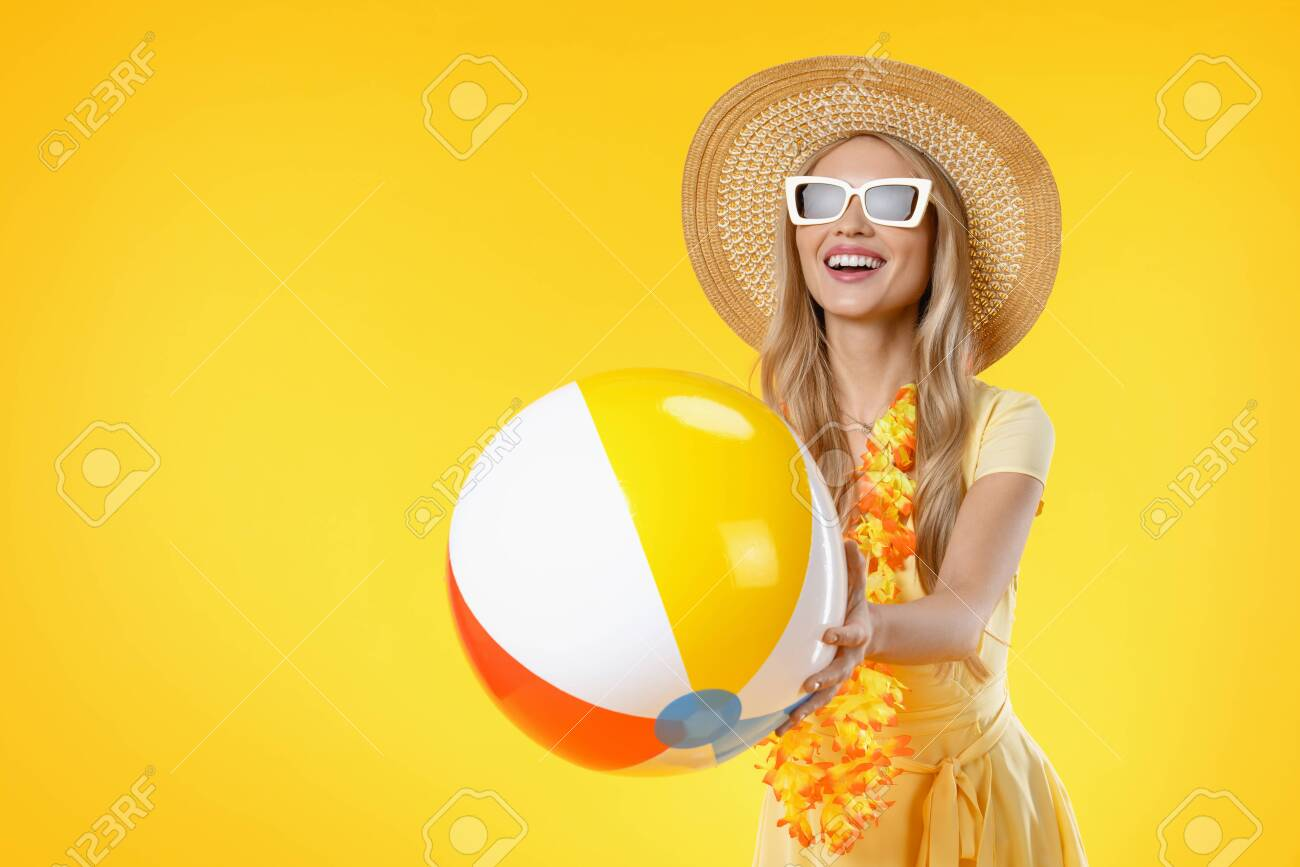 Attractive woman with beach accessories holding colorful ball on yellow background - 138582698