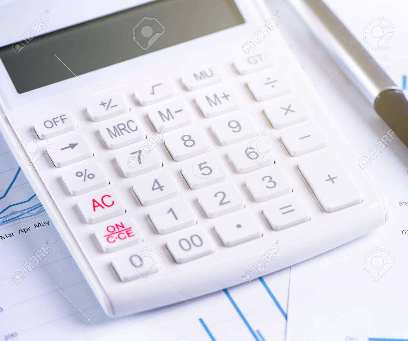 White calculator and report with chart and graph, concept of annual financial profit overview, banking and investment, copy space, macro, close up - 125326911