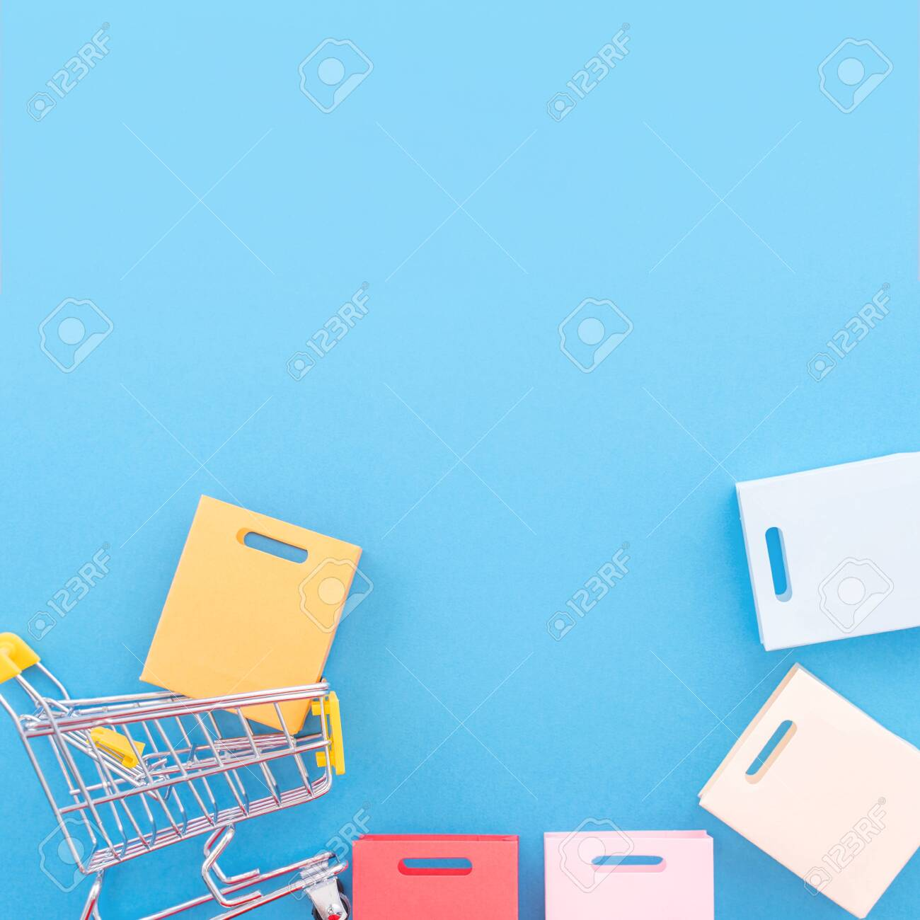 Abstract design element, annual sale, shopping season concept, mini yellow cart with colorful paper bag on pastel blue background, top view, flat lay - 131009060