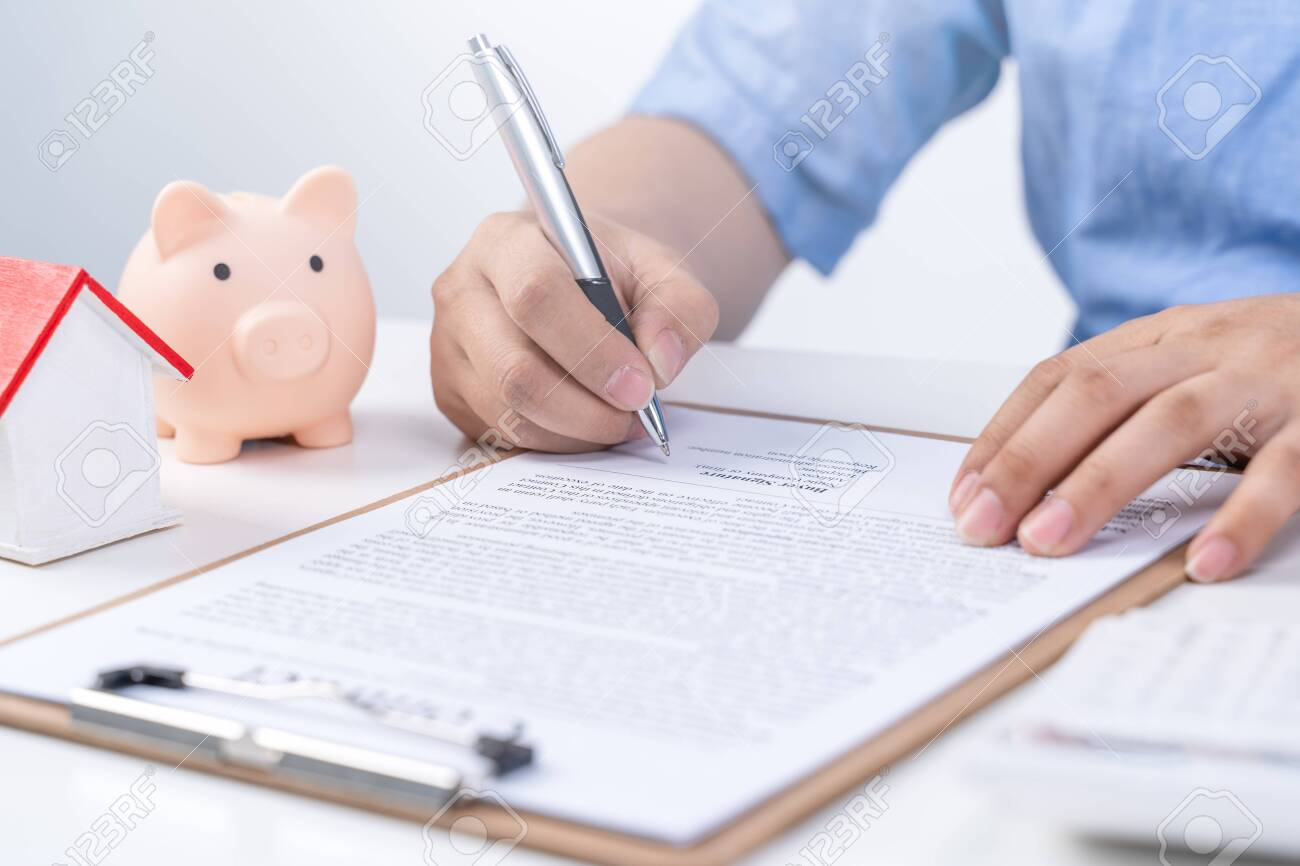 Business concept - Young Asian man in blue shirt calculates, signs agreement contract to buy a house loan payment, paying insurance, tax, close up. - 145124160