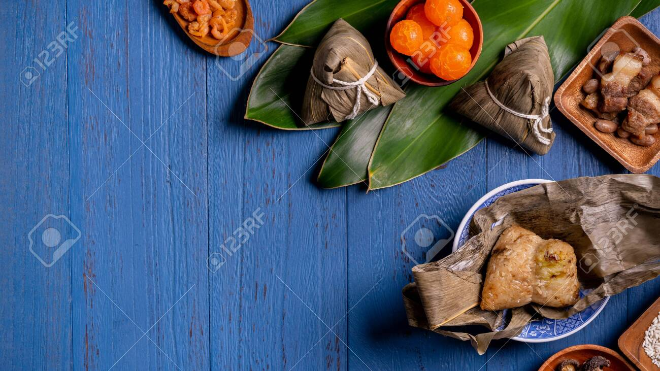 Rice dumpling, zongzi - Traditional Chinese food on blue wooden background of Dragon Boat Festival, Duanwu Festival, top view, flat lay design concept. - 147247229