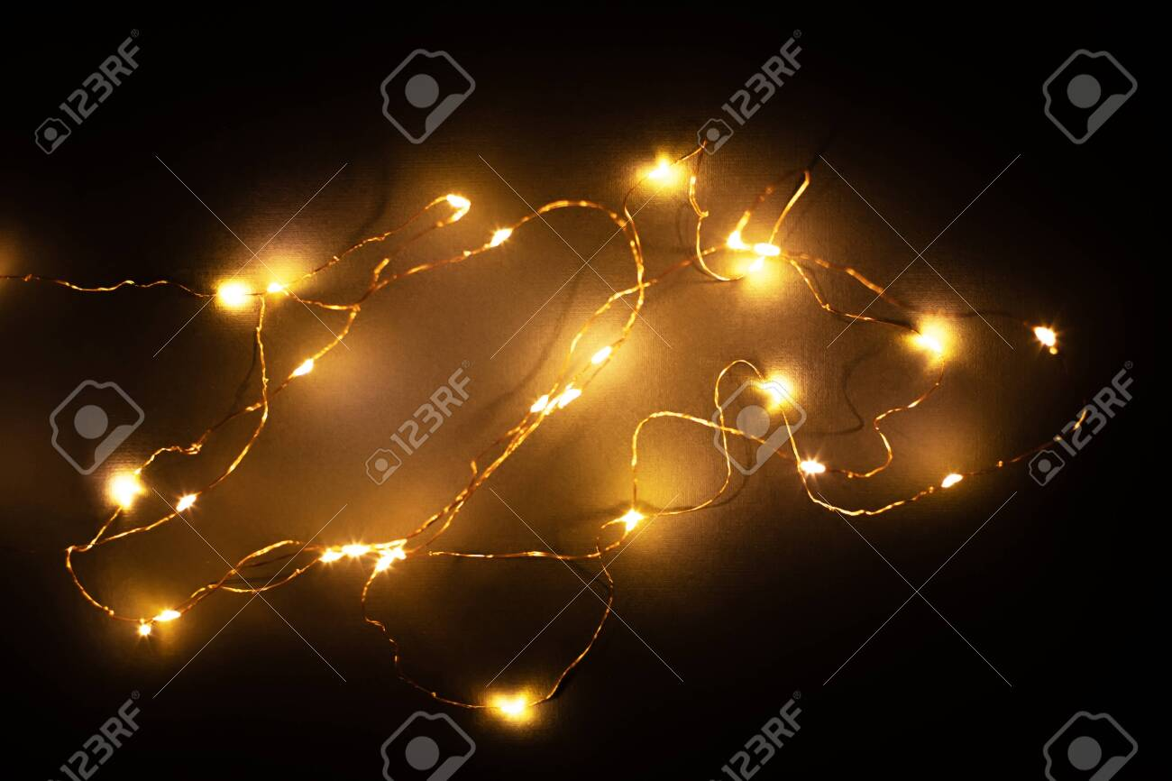 Abstract christmas led lights on black background. Blurred glowing light bulb garland, black layer for screen mode overlays to light up the bulbs. Festive concept - 135441460