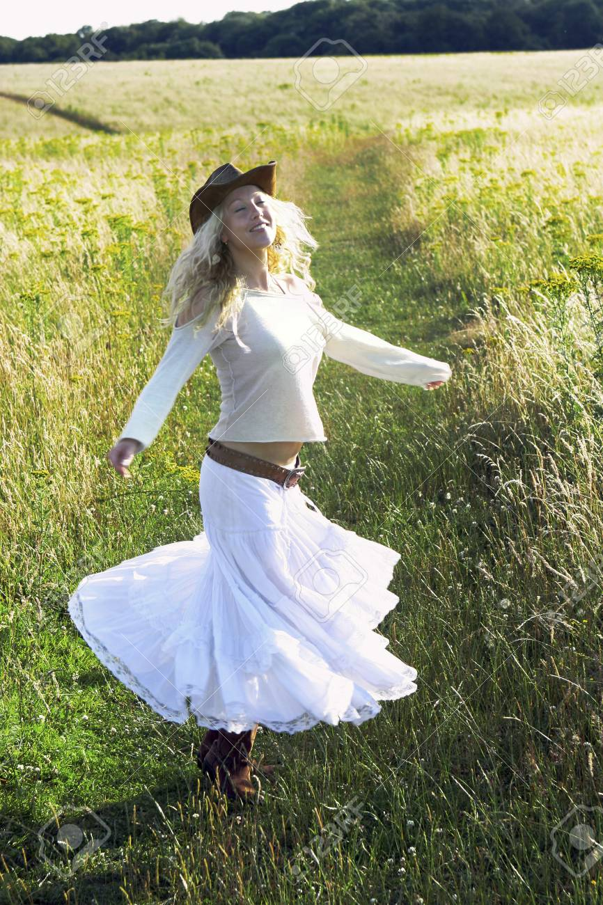 A woman with cowboy hat running on the field Stock Photo - 26131456 7541229e6ba