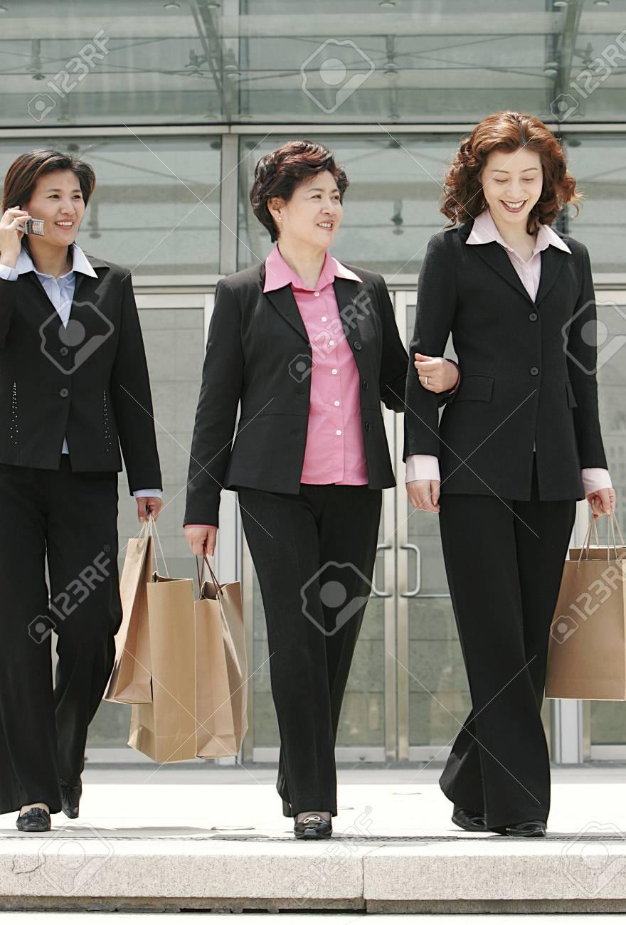 drei damen in abendgarderobe zusammen spazieren trägt papiertüten