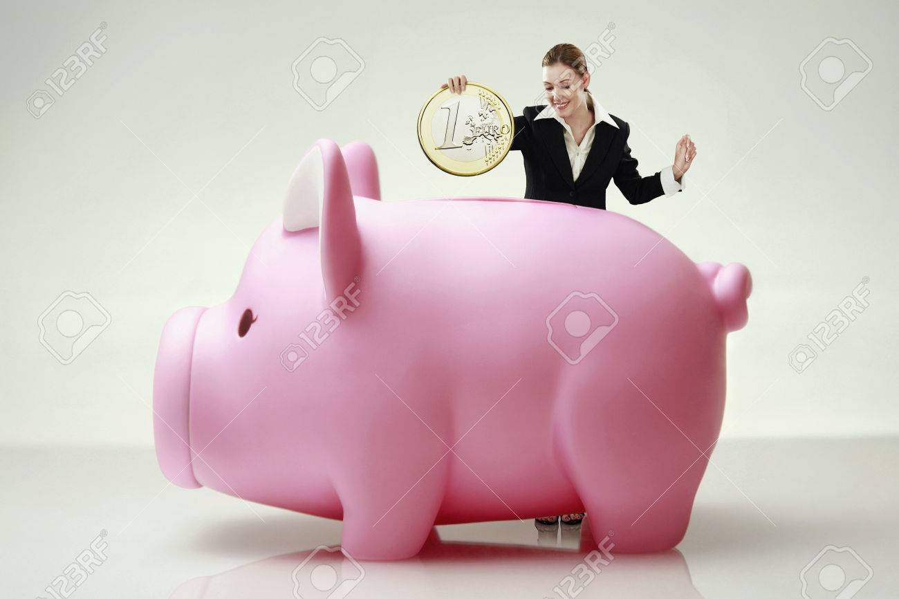 Businesswoman Putting In A Giant Sized Coin Into Piggy Bank S Stock Photo Picture And Royalty Free Image Image 26206058