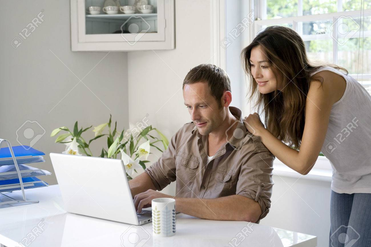 Woman Watching Man Work In A Home Office Stock Photo Picture And