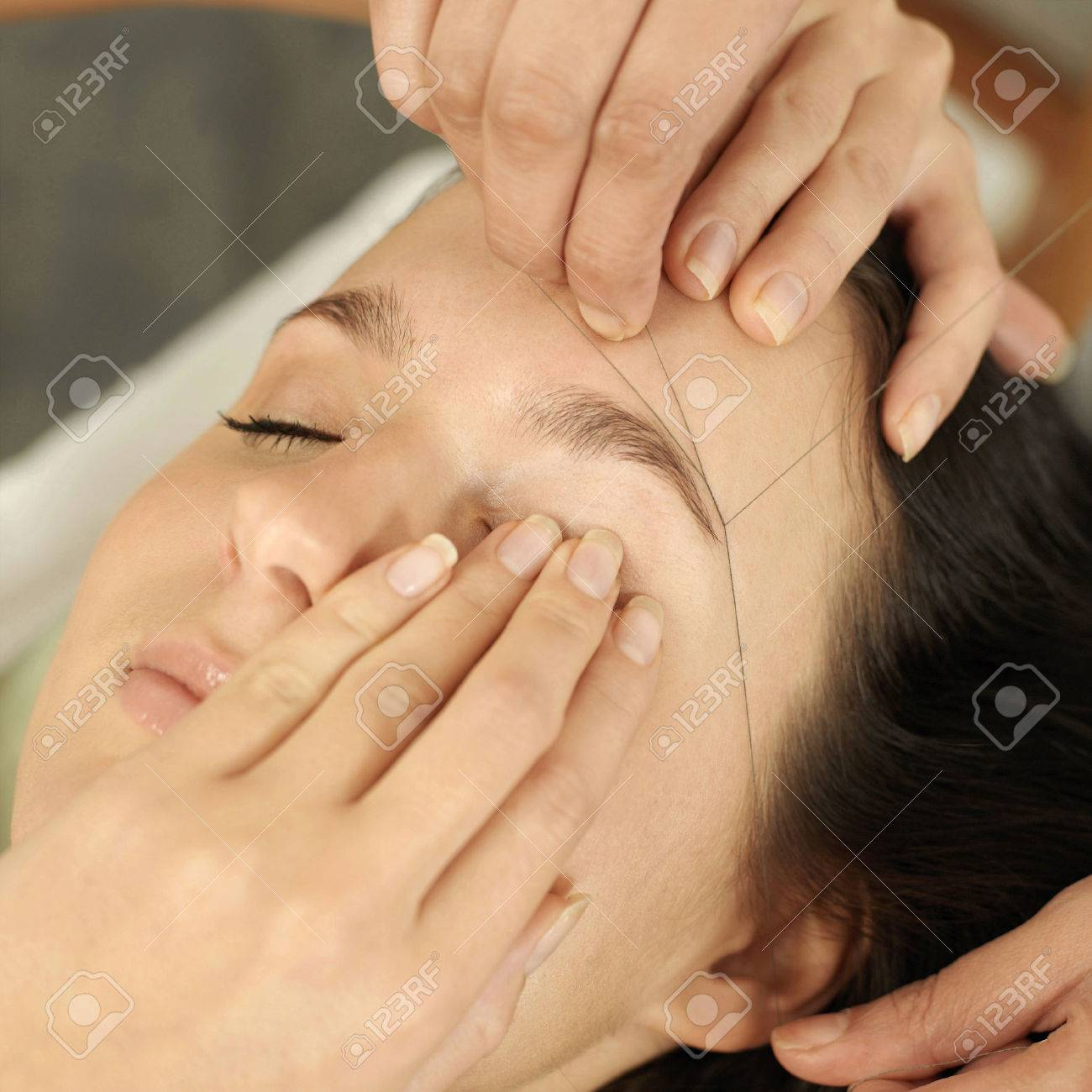 Hand using thread to remove facial hair from woman's face Stock Photo - 26265124
