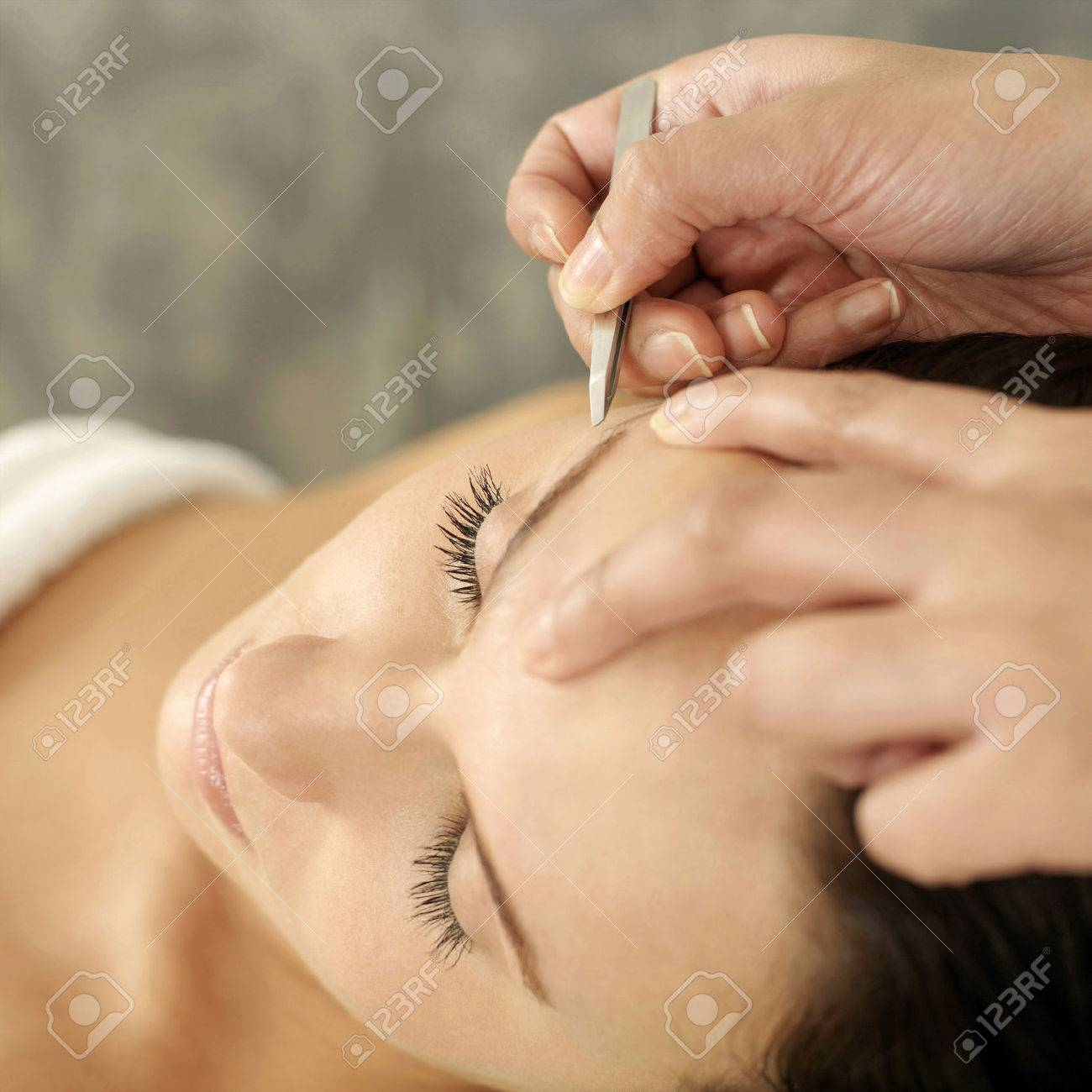 Hand tweezing woman's eyebrow Stock Photo - 26265129