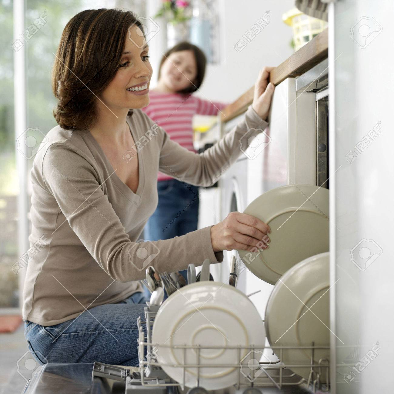 Girl watching her mother keeping the dishes in the dishwasher Stock Photo - 26270641
