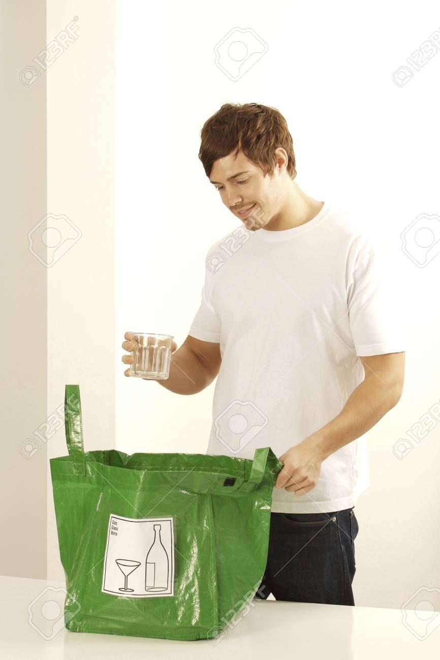 dc7ee20b8 El hombre con el vidrio y bolsa de plástico para su reciclaje Foto de  archivo -