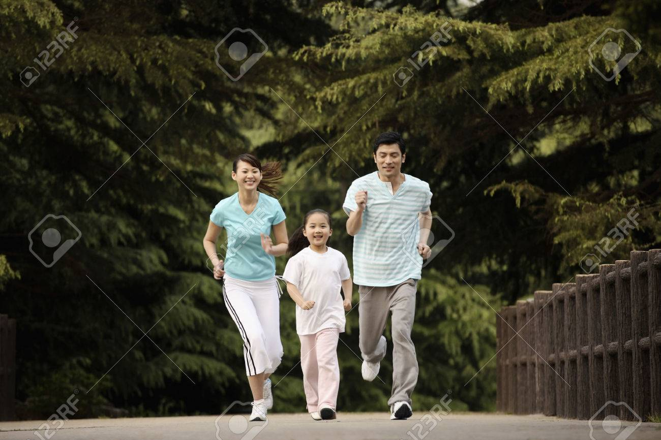 Girl and parents running in the park - 26203378