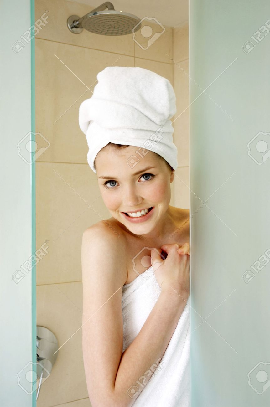 A woman with her hair and body wrapped up in towel hiding behind the shower door Stock Photo - 26382188