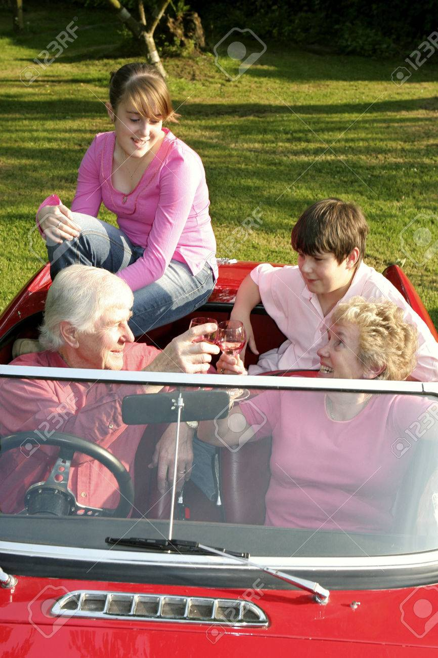 An Old Couple Taking Their Grandchildren For A Car Ride Stock Photo ...