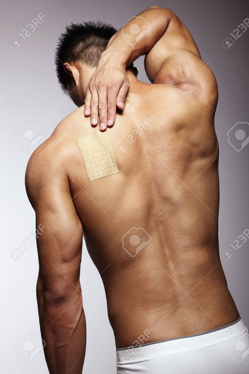Man putting pain relief patch on his back Stock Photo - 26384995