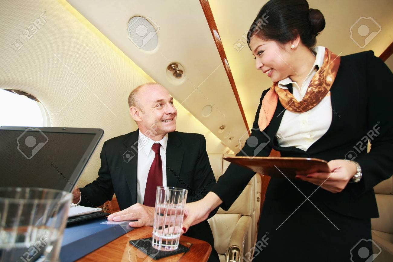 Flight attendant serving businessman a glass of water Stock Photo - 26386109