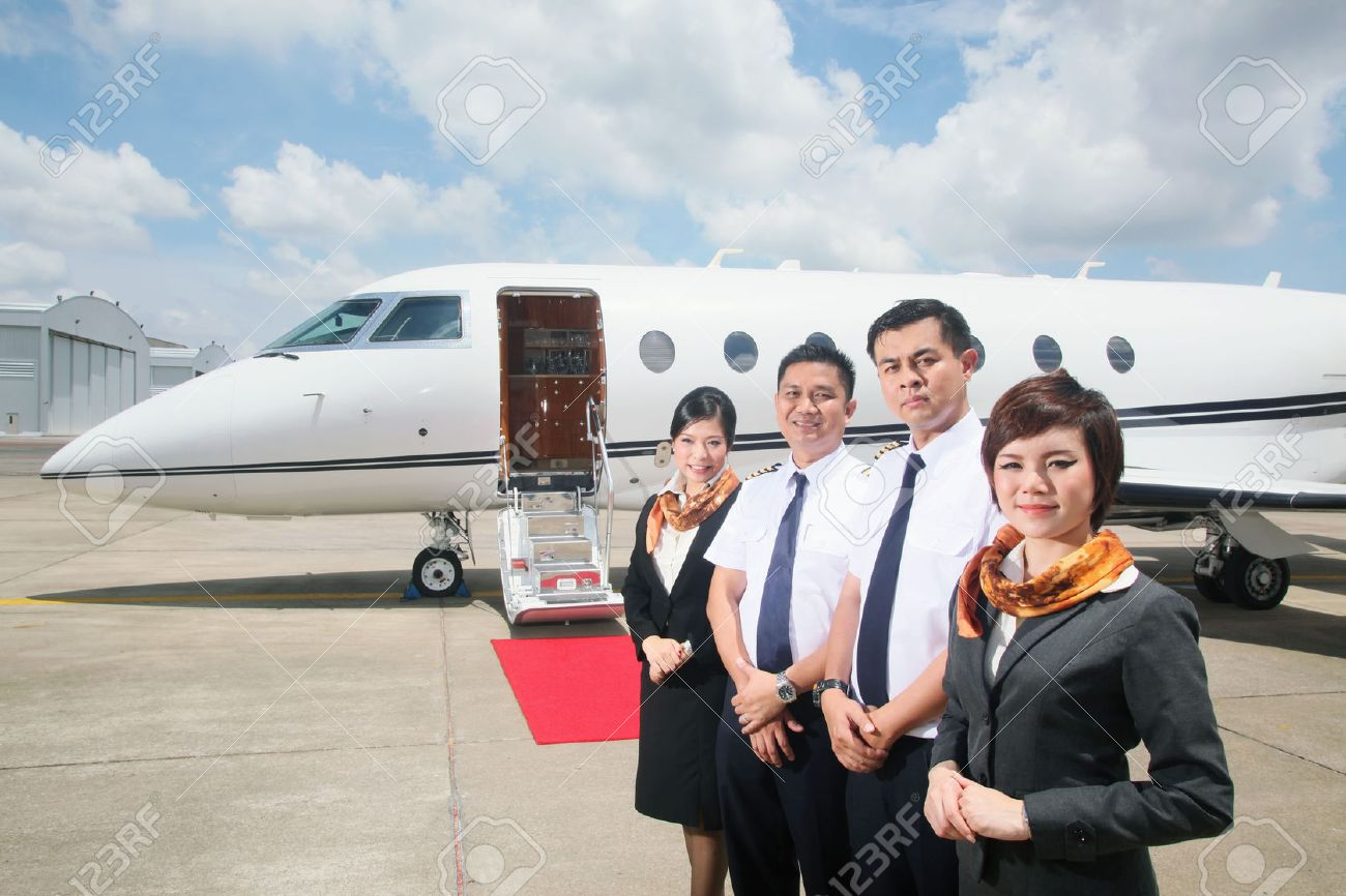 Pilots and flight attendants standing by private jet Stock Photo - 26386155
