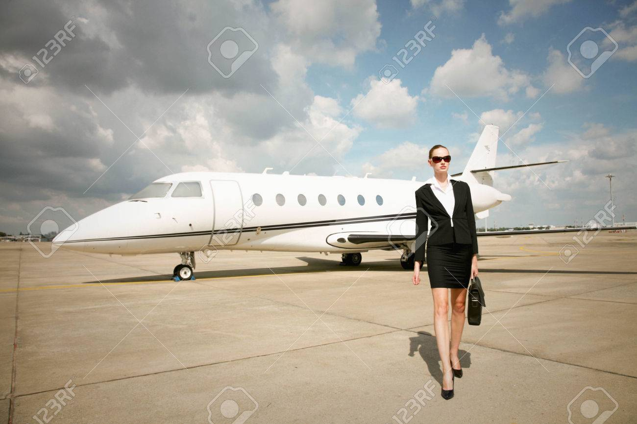 Businesswoman walking at runway with private jet in the background Stock Photo - 26386119
