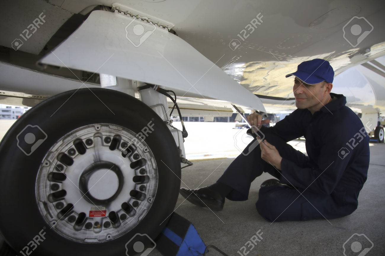 Mechanic examining tire of private jet Stock Photo - 26386185