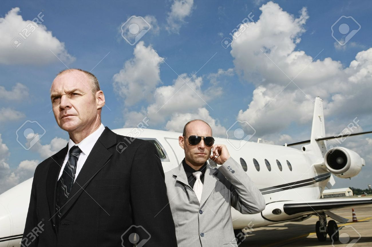 Businessman with his bodyguard and a private jet in the background Stock Photo - 26386189